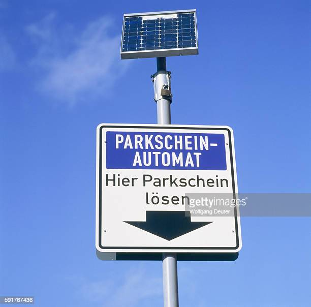 Traffic sign parking ticket dispenser with solar cell against blue sky