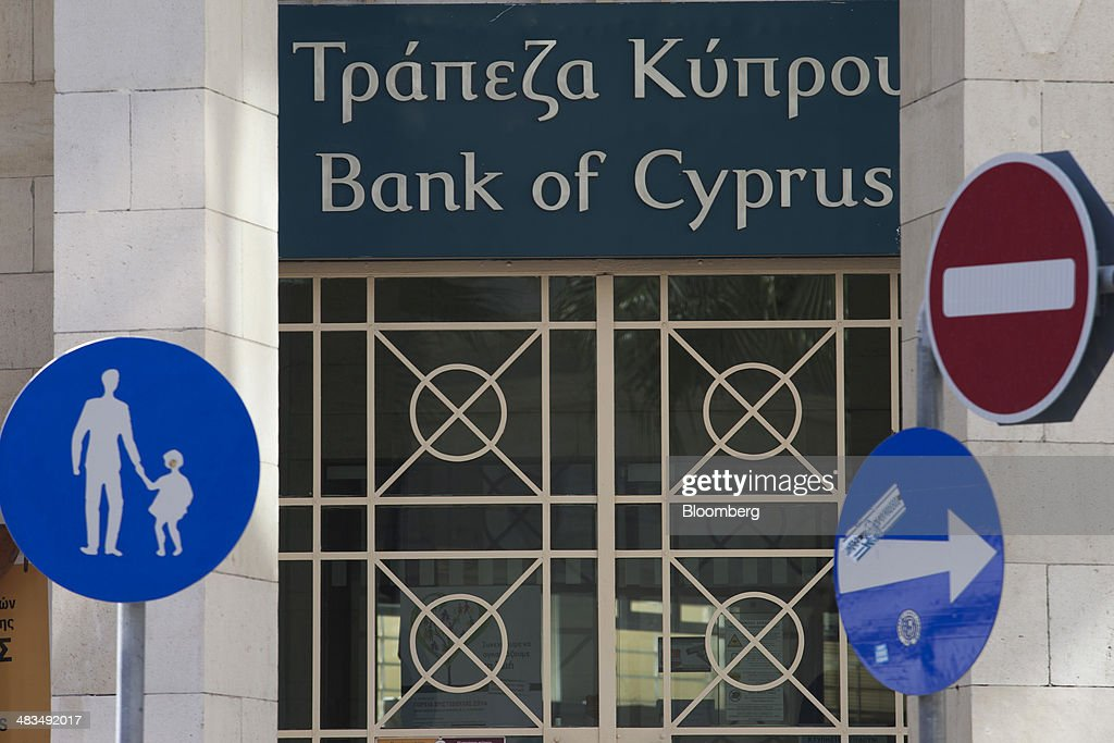 Traffic signs stand on a roadside outside a Bank of Cyprus Plc bank branch in Limassol, Cyprus, on Tuesday, April 8, 2014. Cyprus wants to shield financial flows with Russia, where it's the biggest foreign investor, as the U.S. and the European Union ratchet up sanctions in response to President Vladimir Putin's annexing Crimea from Ukraine. Photographer: Andrew Caballero-Reynolds/Bloomberg via Getty Images