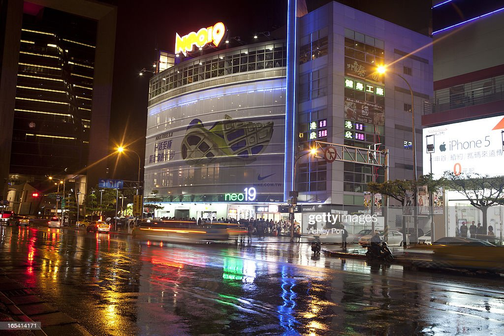 Traffic streams past buildings during a rain storm at the shopping district in Taipei's Hsin-yi district on April 3, 2013 in Taipei, Taiwan. Franchise and chain operations in Taiwan's retail and food sectors make up 50 per cent of sales, and 25 per cent of the service sector.