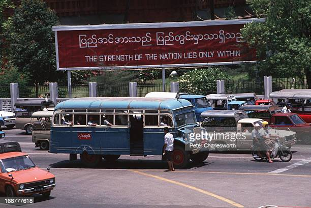 BURMA YANGON RANGOON MYANMAR Traffic waits at a traffic light in front of a billboard sign put up by the ruling military Junta in a street in central...