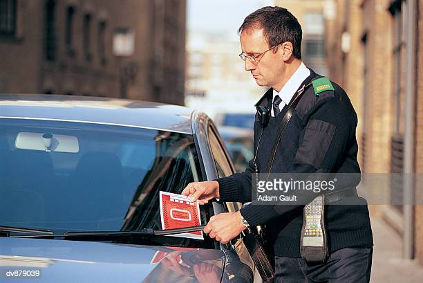 Traffic Warden Attaching a Parking Ticket to a Car's Windscreen