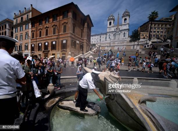 A traffic warden fills up bottles of water off the barcaccia Fountain in Rome's Piazza di Spagna on July 23 2017 Several areas of Italy including the...