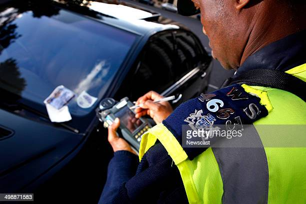 A traffic warden issues a parking ticket