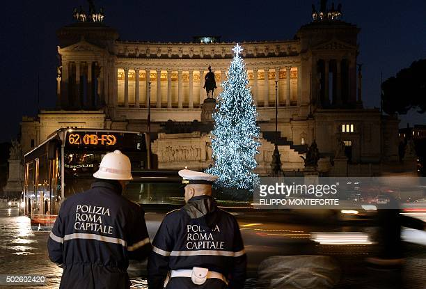 Traffic wardens stand as cars drive pass the Piazza Venezia in central Rome on December 27 2015 Local authorities decided to ban cars with number...