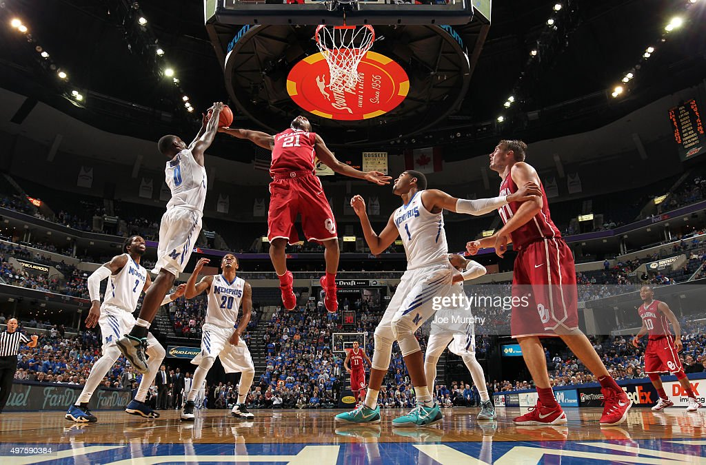 Trahson Burrell of the Memphis Tigers jumps for a rebound against Dante Buford of the Oklahoma Sooners on November 17 2015 at FedExForum in Memphis...