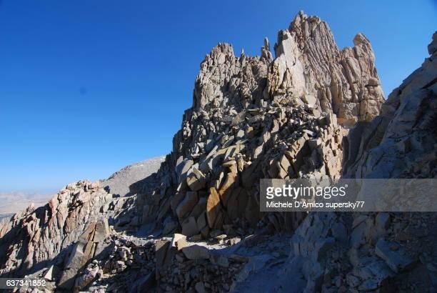 A trail cut in the rock face below jagged granite peaks