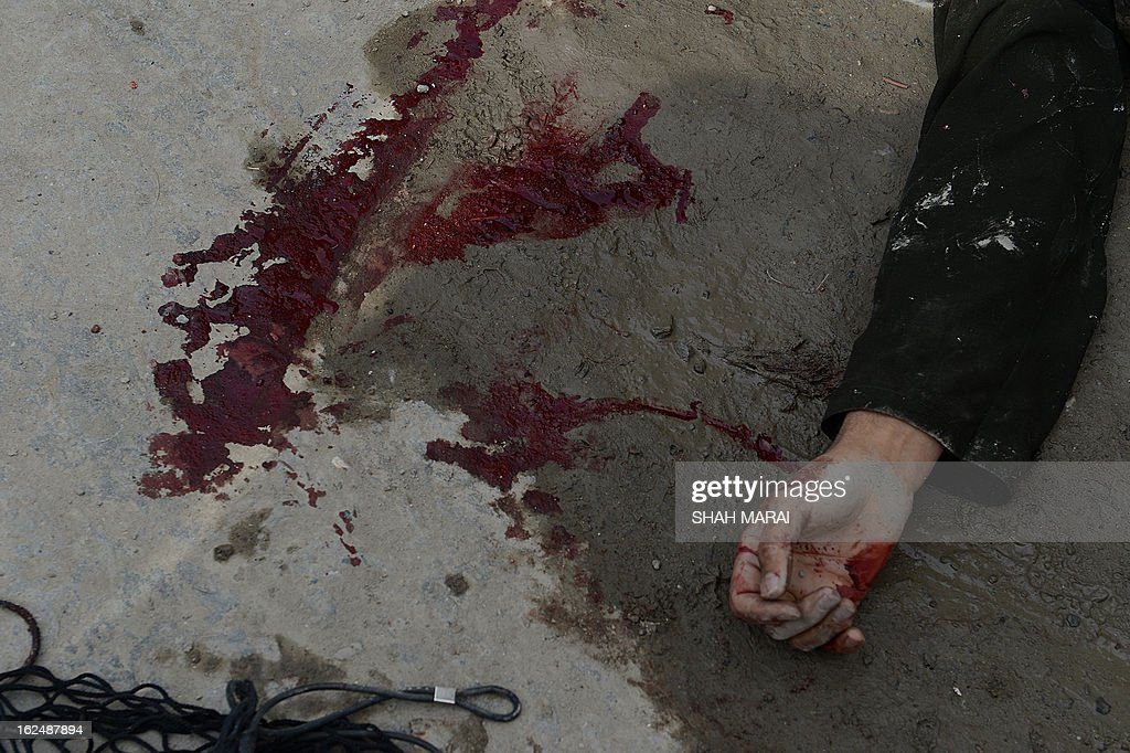 A trail of blood is pictured next to the hand of a suspected suicide bomber in Kabul on February 24, 2013. Afghan security forces on February 24 shot dead one suspected suicide bomber in a car near a construction site in Kabul's diplomatic enclave, a police official and an AFP photographer said. AFP PHOTO/ SHAH Marai
