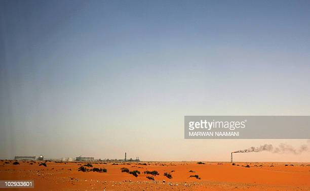 A trail of smoke extends in the wind from the flame of the Saudi Aramco oil installation known as 'Pump 3' in the Saudi Arabian desert near the...