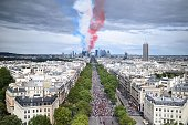 A trail of smoke in the colours of the French national flag is left above the La Defense business district after Alphajet aircrafts from the French...