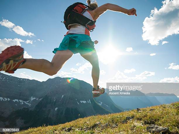 Trail runner bounds along mountain ridge crest