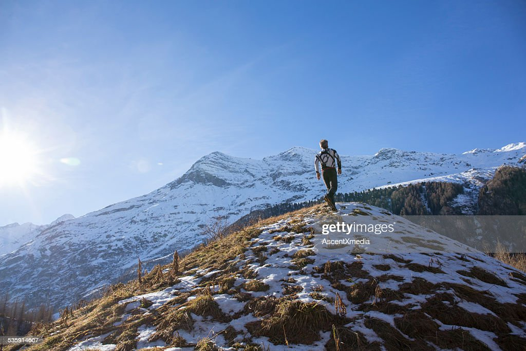 Trail runner bounds up snowy mountain slope : Stock Photo