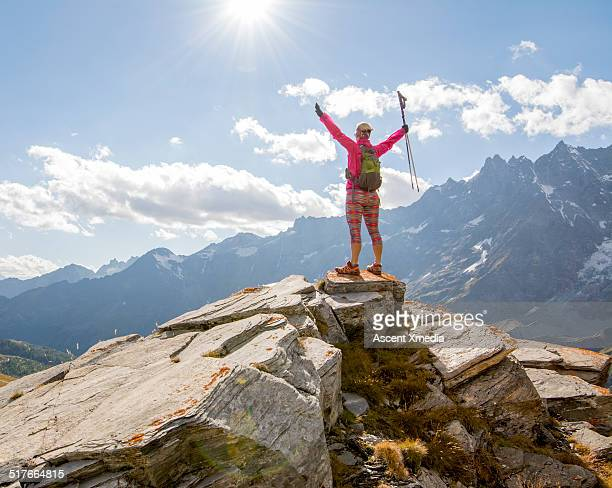 Trail runner stands on mountain summit, arms out