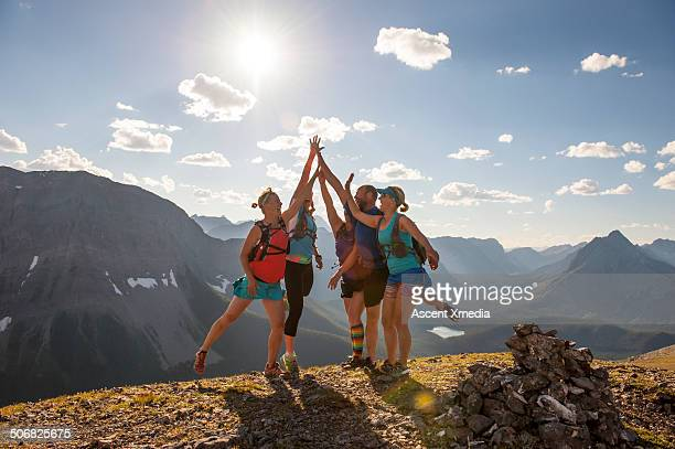 Trail runners exchange high fives on mtn summit