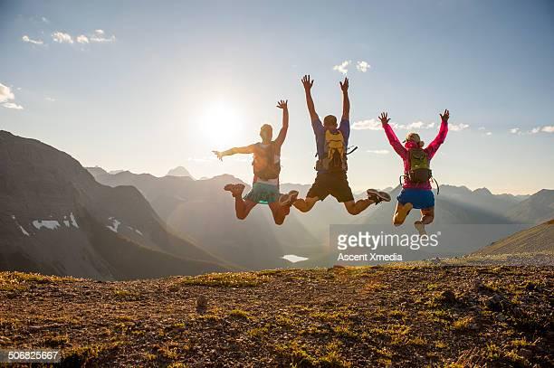 Trail runners in mid-air jump above mountain ridge