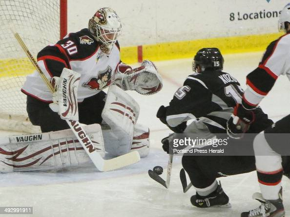 Trailed by Maxim Goncharov of the Portland Pirates Brandon Kozun of the Manchester Monarchs takes a shot at Pirates goalie Chad Johnson during a game...