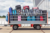 Trailer outside on airport filled with suitcases. When I arrived in Amsterdam on the airport Schiphol I took this image of packed suitcases on a standing trailer. Passengers on vacation take a lot of