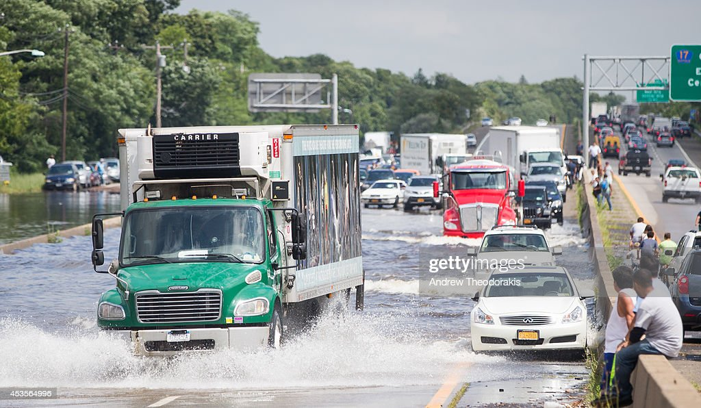 A trailer truck drives past flooded cars abandoned on Sunrise Highway at Route 111 following heavy rains and flash flooding August 13, 2014 in Islip, New York. The south shore of Long Island along with the tri-state region saw record setting rain that caused roads to flood entrapping some motorists.