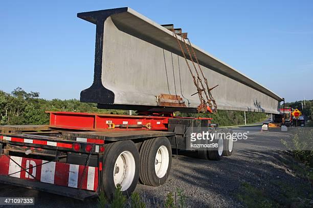 Trailer truck hauling long cement roadway barrier