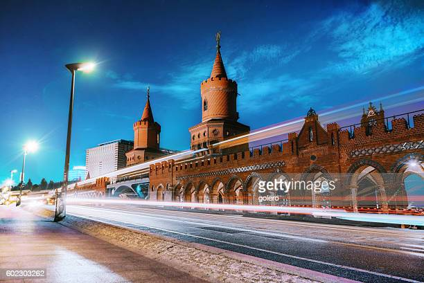 train and cars passing Berlin Oberbaumbrücke at blue hour