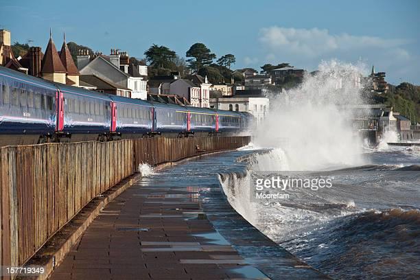 Train arrivant à Dawlish avec des vagues se briser sur la