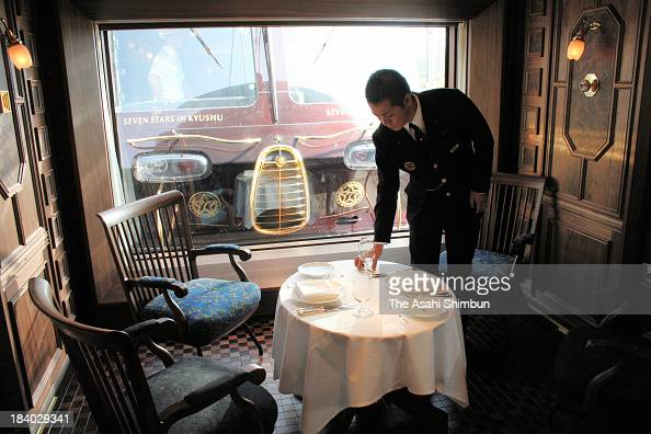 A train attendant practices table setting during the press preview of 'Nanatsuboshi ' luxury sleeper cruise train on October 10 2013 in Kagoshima...
