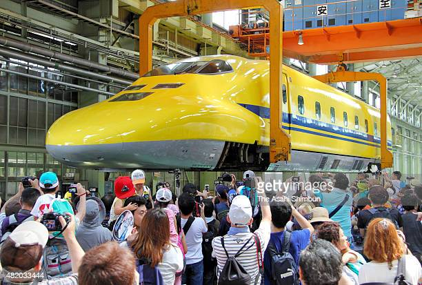 Train buffs take pictures as the 'Dr Yellow' inspection Shinkansen is lifted during a periodic inspection at a factory on July 25 2015 in Hamamatsu...