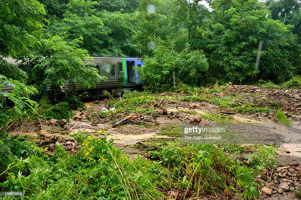 A train carriage sits on the mud covered railway track on August 18, 2013 in Mori, Hokkaido, Japan. Train operation between Sapporo and Hakodate has been suspended due to a landslide triggered by a torrential rain washed the enbankment, hit 'bon' holidaymakers.