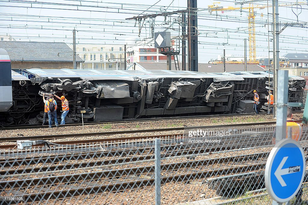 Train carriages derailed in an accident lie within Bretigny-sur-Orge railway station on July 13, 2013 in Bretigny-sur-Orge, France. An intercity train carrying 385 passengers, travelling from Paris towards Limoges, derailed crashing into a station platform leaving six people dead and a further 30 injured on July 12, 2013. French investigators for SNCF have stated that the cause by a fault in the tracks.