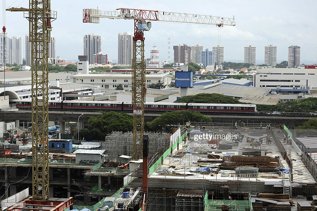 A MRT train, center, passes by CapitaLand Ltd.'s Bedok Residences mixed development project which sits under construction in Singapore, on Monday, Feb. 18, 2013. CapitaLand, Southeast Asia's biggest developer, is scheduled to release fourth quarter earnings on Feb. 21. Photographer: Munshi Ahmed/Bloomberg via Getty Images
