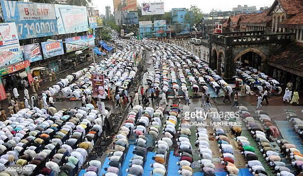 Train commuters walk past devout Indian Muslims offering namazholy prayers on Eid al Fitr outside a busy railway station in Mumbai on September 11...