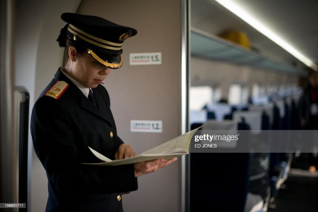 A train conductor stands aboard a high-speed train departing the Beijing West Railway Station in Beijing on December 22, 2012. China showed off the final link of the world's longest high-speed rail route, set to open on December 26, stretching from Beijing to the southern Chinese city of Guangzhou. Travelling at around 300 kph, trains on the new route are expected to cover the 2,298-kilometre (1,425-mile) journey in a third of the current time from 22 hours to eight. AFP PHOTO / Ed Jones