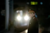 A train conductor stands before a highspeed train at the Beijing West Railway Station in Beijing on December 22 2012 China showed off the final link...