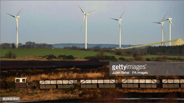 A train crossing a bog passes in front of a wind farm while carrying peat to the Bord na Mona Peat Briquettes manufacturing factory at Littleton in...