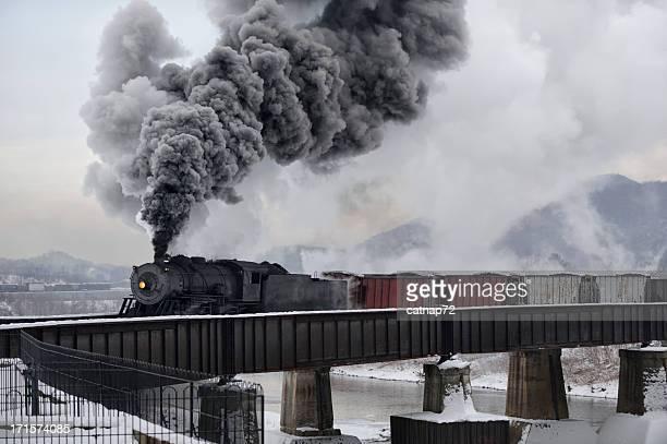 Treno attraversando il fiume Ponte vecchia ferrovia a vapore locomotiva in inverno
