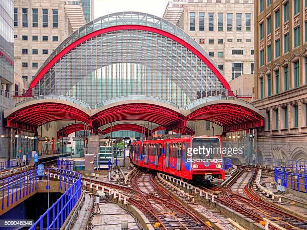 DLR train departs distinctive Canary Wharf station in rain