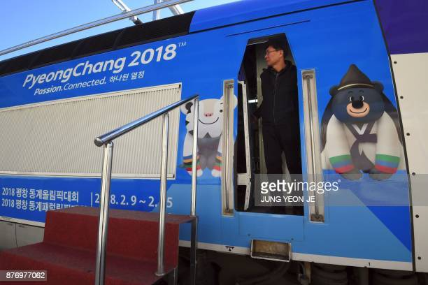 A train driver looks out from a KTX bullet train decorated with the mascots of the 2018 PyeongChang Winter Olympics during a press tour of the new...