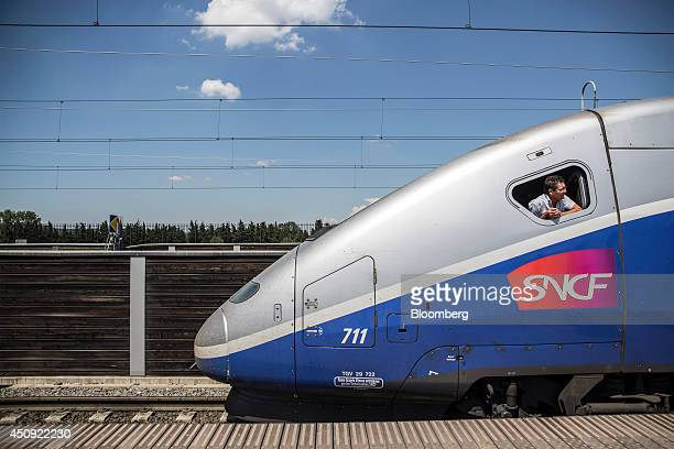 A train driver looks out of the cab window as passengers board a TGV duplex highspeed train operated by Societe Nationale des Chemins de Fer and...