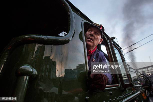 A train driver looks out of the window of The Flying Scotsman as it leaves Kings Cross Station on February 25 2016 in London England The Flying...