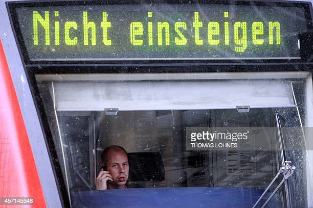 A train driver speaks on a phone as a sign above his windscreen reads 'don't get on' at Frankfurt/Main's railway station 05 October 2007 A strike by...