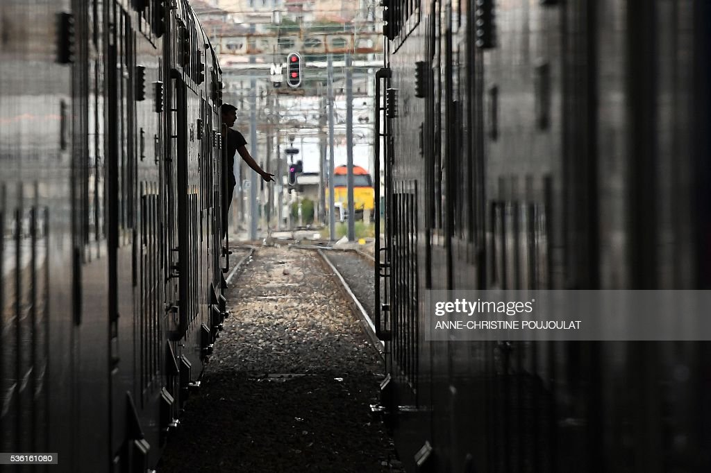 A train driver waits for his train's departure time in the Saint-Charles rail station in Marseille, southeastern France, on May 31, 2016, at the start of a strike by employees of French state-owned rail operator SNCF to protest against government labour reforms. France is bracing for a week of severe disruption to transport after unions called for more action in their bitter standoff with the Socialist government over its labour market reforms. / AFP / ANNE