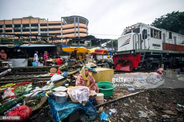 A train engine slowly makes its way past Indonesians who have set up a makeshift market to sell products along a railway line in Surabaya in eastern...