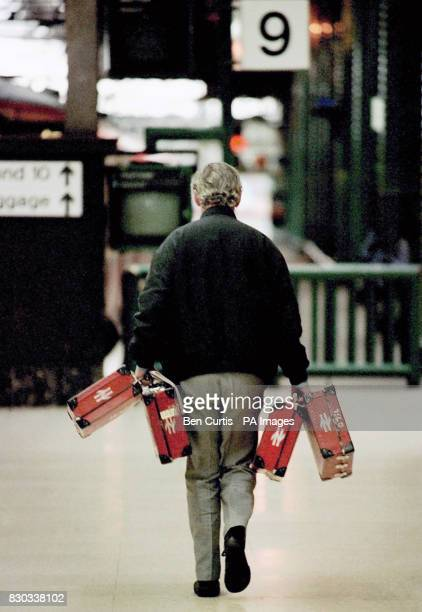 A train guard carries ticket machine boxes along the platform at Glasgow Central Station as guards in the Rail Maritime and Transport union were...