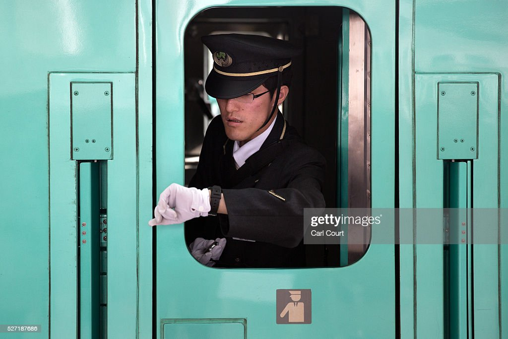 A train guard checks his watch ahead of departure as he leans out of a window on a Shinkansen bullet train at Tokyo Train Station on May 02, 2016 in Tokyo, Japan. The Shinkansen is a network of high-speed railway lines in Japan currently consisting of 2,764.6 km (1,717.8 mi) of lines with maximum speeds of 240-320 km/h (150-200 mph). The network presently links most major cities on the islands of Honshu and Kyushu, and Hakodate on northern island of Hokkaido. The maximum operating speed is 320 km/h (200 mph) though test runs have reached up to a world record 603 km/h (375 mph) for maglev trains in April 2015.