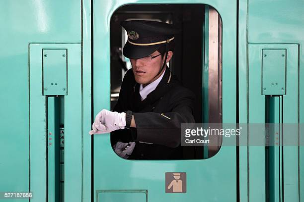 A train guard checks his watch ahead of departure as he leans out of a window on a Shinkansen bullet train at Tokyo Train Station on May 02 2016 in...