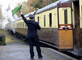train guard signaling for old steam train to depart from platform, last chance to board