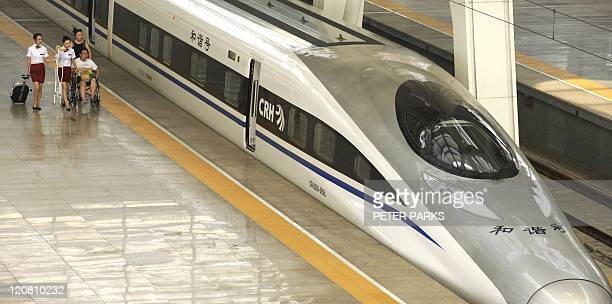 Train hostesses help a man in a wheelchair next to a high speed train at Beijing south railway station on August 11 2011 China has suspended all new...
