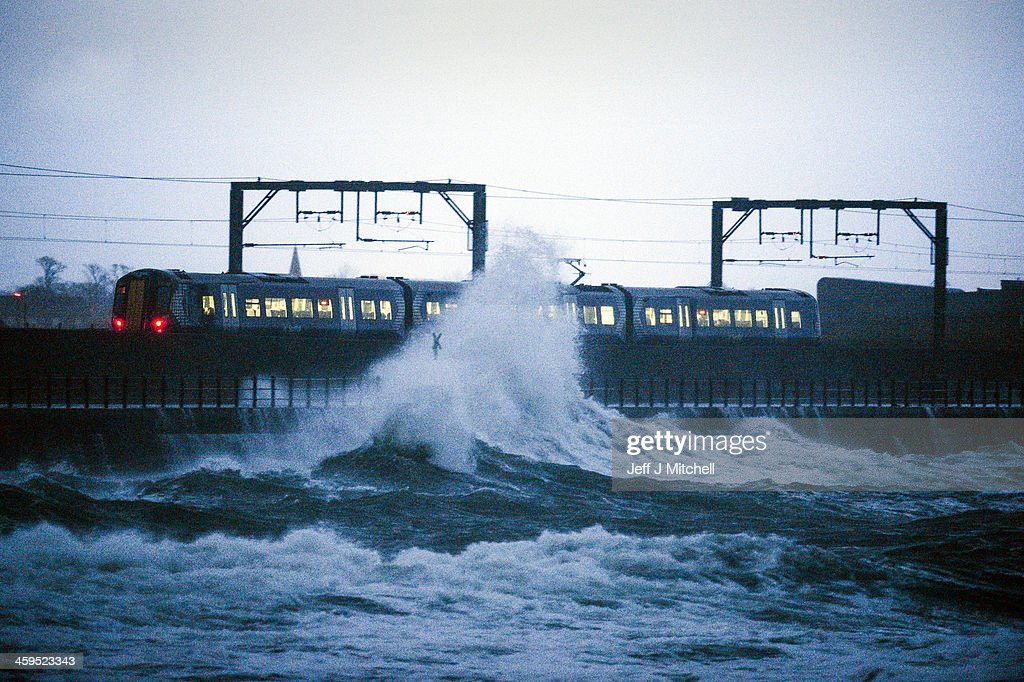 A train leaves Saltcoats station as a large wave crashes nearby on December 27, 2013 in Saltcoats, Scotland. A yellow 'be aware' warning has been issued for many parts of Scotland as the country is affected by gale force winds and heavy rain.