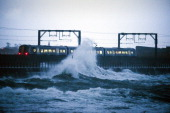 A train leaves Saltcoats station as a large wave crashes nearby on December 27 2013 in Saltcoats Scotland A yellow 'be aware' warning has been issued...