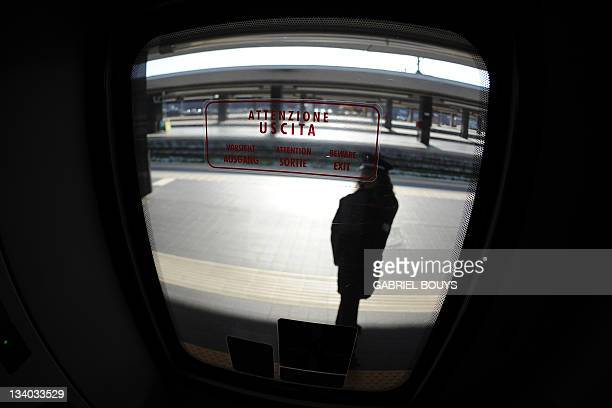 A train manager stands on the platform near a Freccia Rossa highspeed train at Rome's Termini station on 24 November 2011 AFP PHOTO / GABRIEL BOUYS