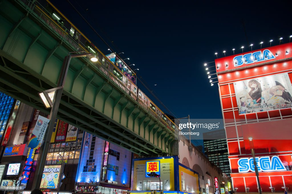 A train moves along an elevated track past an advertisement for Sega Corp., right, in the district of Akihabara in Tokyo, Japan, on Wednesday, Feb. 13, 2013. Japan's economy unexpectedly shrank last quarter as falling exports and a business investment slump outweighed improved consumption, highlighting the challenge facing Prime Minister Shinzo Abe as he seeks to end deflation. Photographer: Noriko Hayashi/Bloomberg via Getty Images